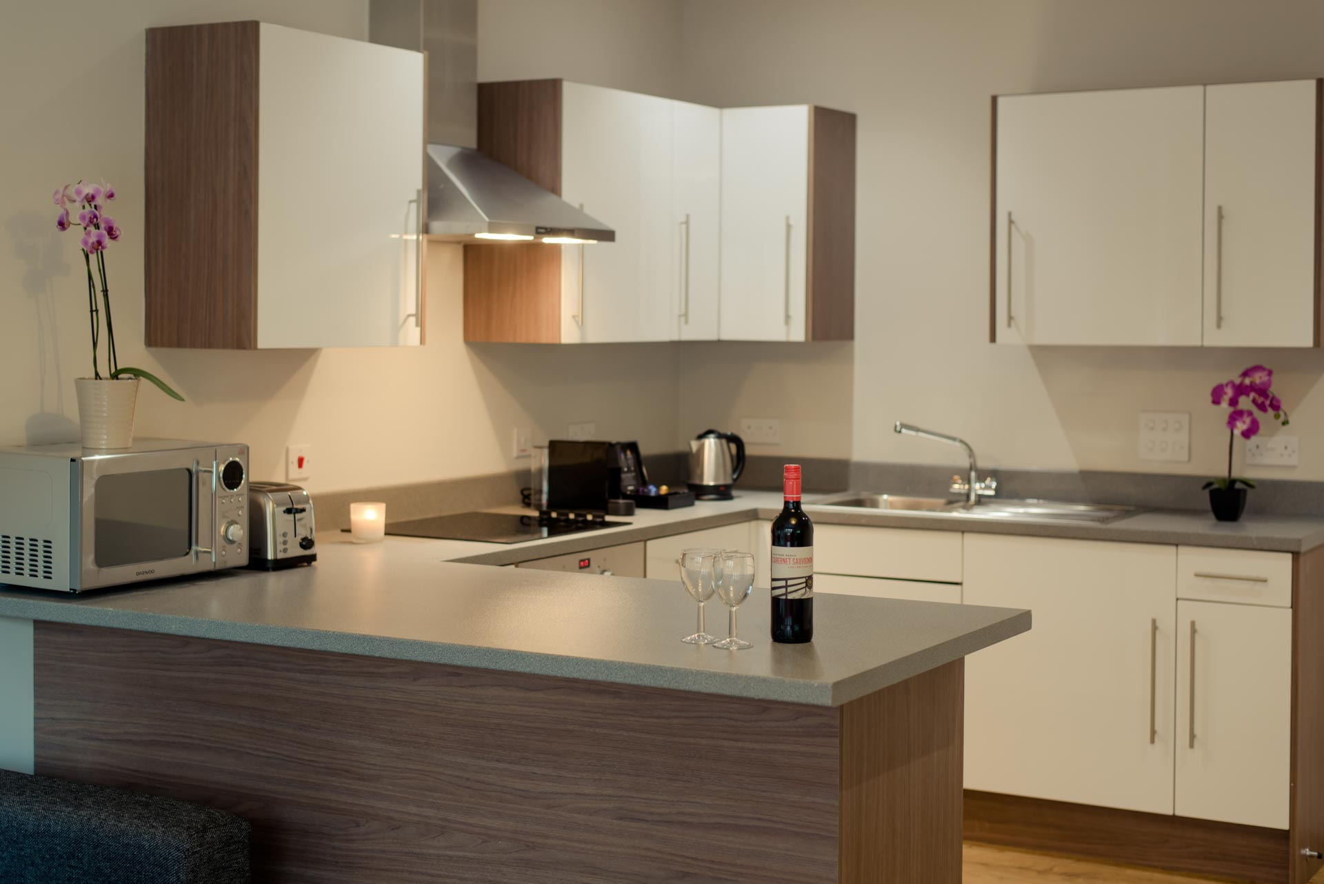 Kitchen counter top with red wine and glasses PREMIER SUITES PLUS Glasgow Bath Street